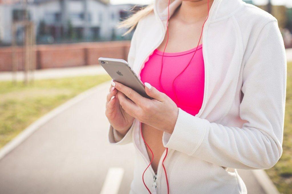 スマホを持ちながら運動する女性